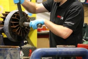 Hand on spanner on Speck pump repair